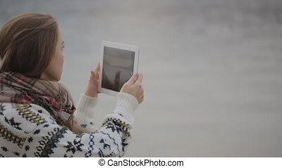 The young woman is taking the pictures of the nature using the tablet pc.