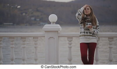 The young beautiful woman is standing on the quay with the...