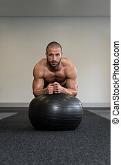 Young Man Exercising With Fitness Ball Abs Exercise