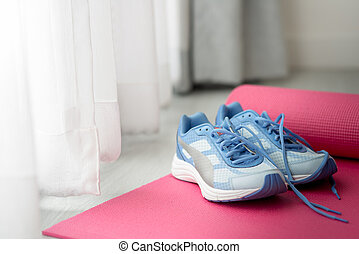 blue sport shoes on pink yoga mat with nature light in the morning.