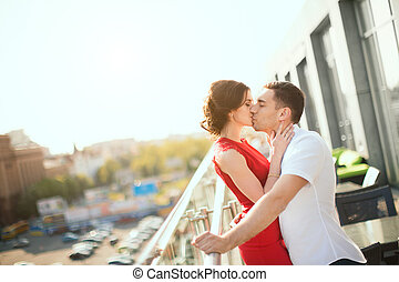 Happy young couple embraces against view of the city -...