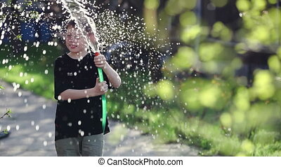 Boy playing with water from a hose.