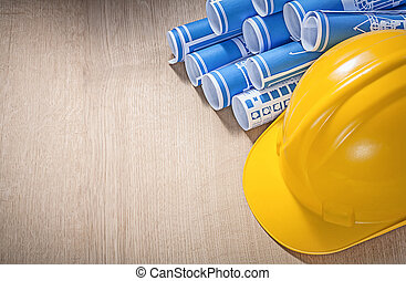 Blue rolled blueprints hard hat on wooden board construction con