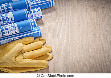 Blue rolled construction drawings leather safety gloves on...