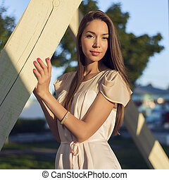 Happy brunette woman dress relaxing fun leaning on wooden piles park enjoy your vacation, fashion style urban life.