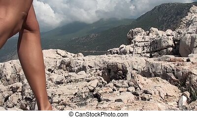 Walking on cliffs - A woman is walking on cliffs barefooted,