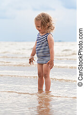 Pretty child playing in the ocean, summer time
