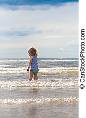 Pretty child playing - Little child standing in the sea,...