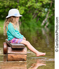 Cute girl sitting on the bank