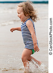 Pretty child playing - Young child playing in the waves,...
