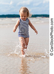Pretty child playing - Cute child running in the waves,...