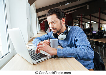 Man using laptop computer in office - Handsome man using...