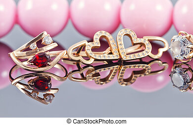 Various Golden ornaments on a background of pink beads