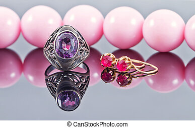 Silver ring with amethyst and gold earrings with a ruby on a...