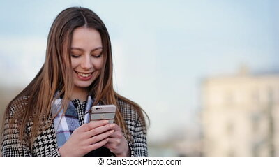 Attractive young woman using her smartphone and smile in the...