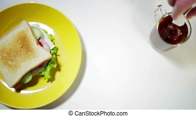 Sandwich on yellow plate and cap of tea kitchen - Sandwich...