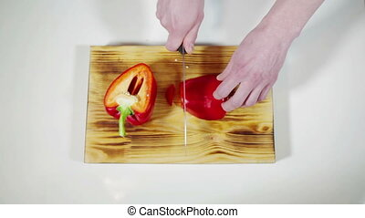 Man slicing red bell pepper on a cutting board Music kitchen...