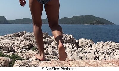 Woman walking on cliffs - A woman in bathing suit is walking...