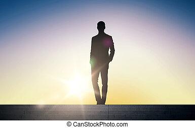 silhouette of businessman over sun light