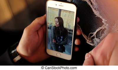 Close up of male hands using smartphone to see his girlfriend`s picture in more details.