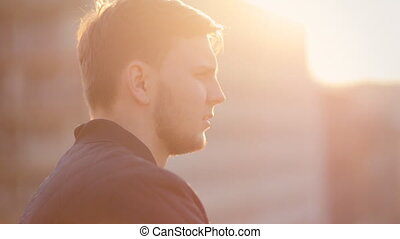 Young man on the balcony watching the sunset Close up