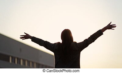 Adorable woman in fashionable coat relaxing on the balcony taking her hands up to the sky.