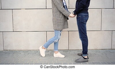 Young happy couple kissing on camera and talking to each other in the street .