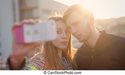 Young happy couple taking selfies in the street .