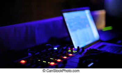 A DJ console in the night club - DJ uses the console to mix...