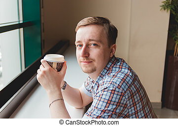 Young man taking a coffee break at cafe smiling