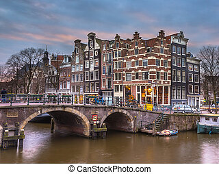 Canal houses at sunset in Amsterdam - Old traditional canal...