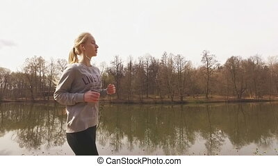 Runner woman running in park exercising outdoors fitness...