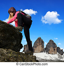 Girl on rock, in the background Tre Cime di Lavaredo -...