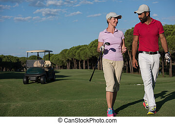 couple walking on golf course