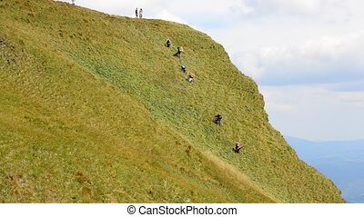 People with rucksacks climb a hill in Carpathians, Ukraine