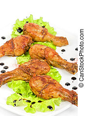 chicken drumstick closeup at white plate with lettuce