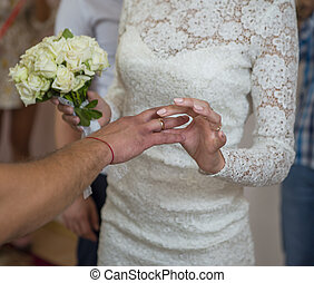 Hands of the groom and bride is wearing a ring on the finger on the day of the wedding ceremony.