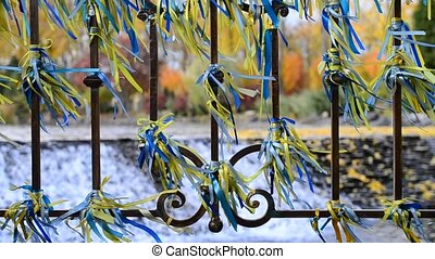Blue and yellow ribbons tied to an iron fence blown by wind...