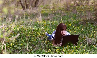 Woman working at a laptop lying on the meadow - Beautiful...