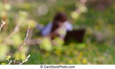 She speaks at a laptop lying down - Beautiful girl with...