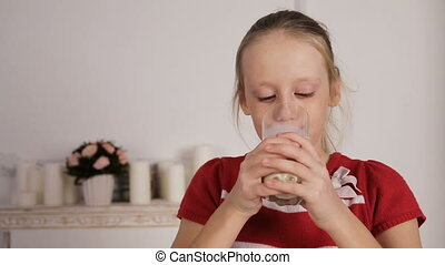 Child drinking glass of milkGirl with dringking milk with...