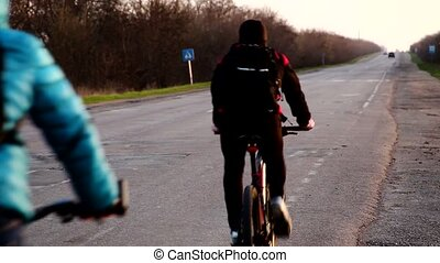 Cyclist riding a bike on an open road to the sunset Early...