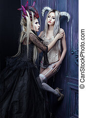 Two women with horns on their heads. - Two women in gothic...
