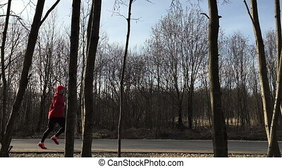 Athlete in red to clothes runs on asphalt and the camera removes him being in the forest.