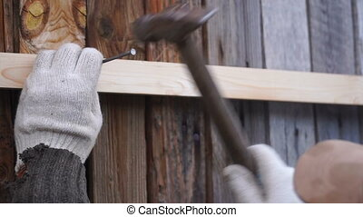 footage man hammers a nail into a plank. Full hd video