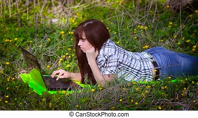 Woman resting at a laptop lying on the meadow