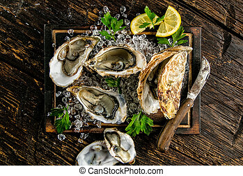 Oysters served on wooden board with ice drift, knife, napkin...