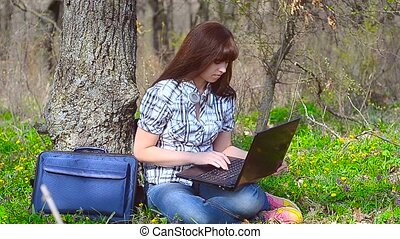 The girl sits at a laptop and laughing