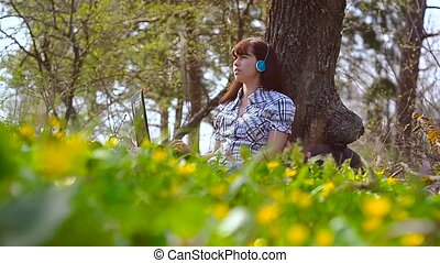 Girl with headphones listening to music at laptop