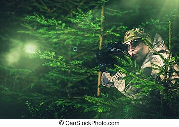 Hunting Poacher in Dense Pine Forest. Hunter in Camouflage...